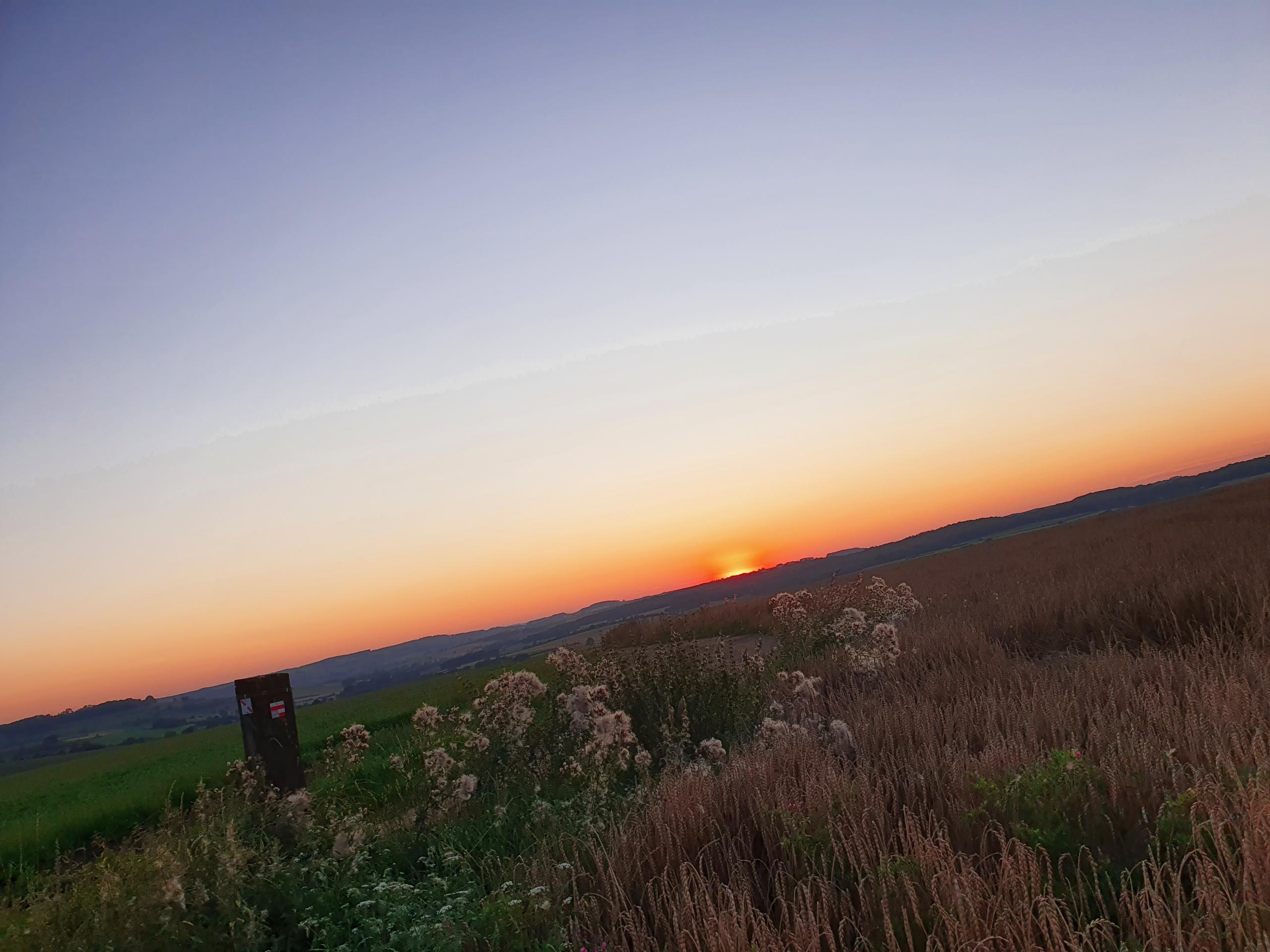 De zon zakt weg achter de heuvels